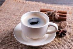 Taza de café con los tubos del canela en la tabla de madera Imagen de archivo libre de regalías