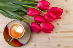 Taza de café con los tulipanes rojos Foto de archivo libre de regalías