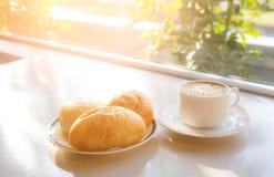 Taza de café con pan en la tabla Fotografía de archivo libre de regalías