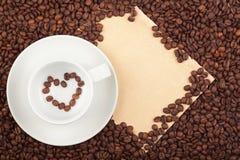 Taza de café con símbolo y el papel del corazón Foto de archivo