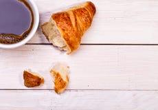 Taza de café con un cruasán Fotografía de archivo