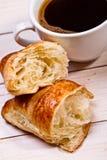 Taza de café con un cruasán Foto de archivo