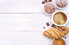 Taza de café con un cruasán y una torta Foto de archivo