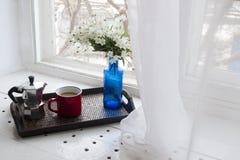 Taza de café con un florero azul en una bandeja de madera cerca de la ventana Foto de archivo