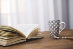 Taza de café con un libro Imagen de archivo libre de regalías