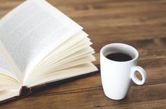 Taza de café con un libro en la tabla de madera rústica Imagen de archivo