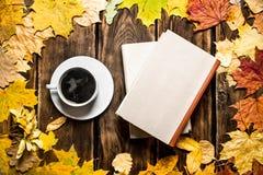 Taza de café con un libro viejo y las hojas de arce Fotografía de archivo