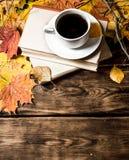 Taza de café con un libro viejo y las hojas de arce Fotografía de archivo libre de regalías