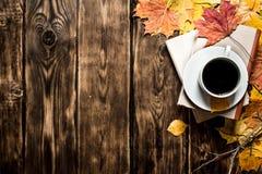 Taza de café con un libro viejo y las hojas de arce Fotos de archivo libres de regalías
