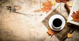 Taza de café con un libro viejo y las hojas de arce Imagenes de archivo