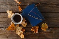 Taza de café con un libro viejo y las hojas del roble En backgro de madera Fotografía de archivo