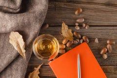Taza de café con un libro viejo y las hojas del roble En backgro de madera Imagen de archivo
