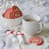 Taza de café con un muñeco de nieve de la melcocha y las galletas bajo la forma de espiral en la tabla de la Navidad Desayuno aco imágenes de archivo libres de regalías