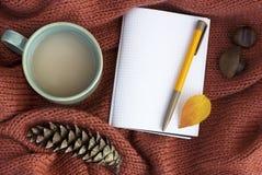 Taza de café con una hoja, una libreta y conos del otoño en un primer hecho punto del suéter, visión superior, espacio de la copi imagen de archivo libre de regalías