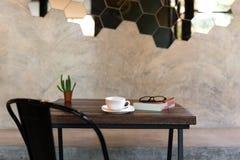 Taza de café conceptual con el libro y vidrios y planta verde encendido Imagenes de archivo