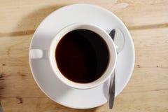 Taza de café contra la tabla de madera Imagen de archivo libre de regalías