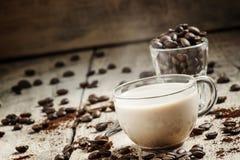 Taza de café de cristal con la leche, el grano derramado y el café molido o foto de archivo libre de regalías