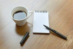 Taza de café, cuaderno espiral y pluma en el backgr laminado del piso foto de archivo