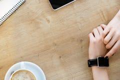 Taza de café, cuaderno, reloj en la tabla Imagenes de archivo
