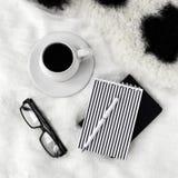 Taza de café, de cuadernos, de pluma y de lentes en la cama Imagenes de archivo