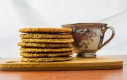 Taza de café cubierta con un stroopwafel y un grupo de stroopwafels foto de archivo libre de regalías