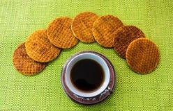 Taza de café cubierta con un stroopwafel y un grupo de stroopwafels imagenes de archivo