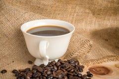 Taza de café de Americano y de granos de café con el backgr de la tela del saco Fotos de archivo