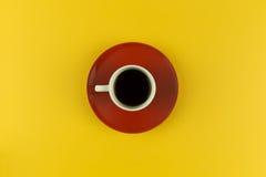 Taza de café de arriba en fondo amarillo brillante Foto de archivo libre de regalías