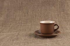Taza de café de Brown en la arpillera fotos de archivo libres de regalías