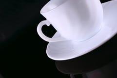 Taza de café de cerámica con un platillo sobre el vidrio oscuro Fotografía de archivo