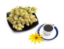 Taza de café, de flor amarilla y de placa con la uva Imagen de archivo