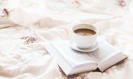 taza de café de la Aún-vida y un libro en cama Foto de archivo libre de regalías