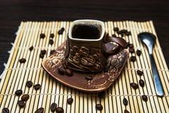 Taza de café de la arcilla con los granos de café fotografía de archivo libre de regalías