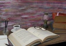 Taza de café de la linterna de tormenta de los libros viejos, compás, vidrios y lápiz Fotografía de archivo