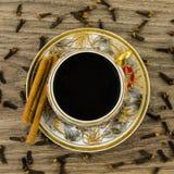 Taza de café de la porcelana con canela y clavos Imagenes de archivo