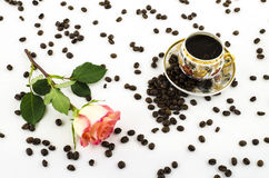 Taza de café de la porcelana con los granos color de rosa de la flor y de café Foto de archivo