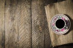 Taza de café de la porcelana en la tabla de madera foto de archivo