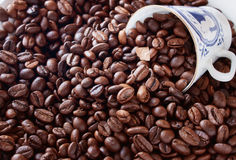 Taza de café de la porcelana fina contra los granos del fondo Fotografía de archivo libre de regalías