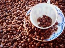 Taza de café de la porcelana fina contra los granos del fondo Imágenes de archivo libres de regalías