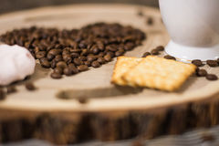 Taza de café de los granos de café en un corte de madera Fotografía de archivo