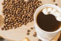Taza de café de los granos de café en un corte de madera Fotografía de archivo libre de regalías