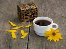 Taza de café, de pétalos, de ataúd y de flor amarilla, aún vida, encendido Foto de archivo