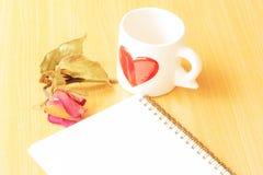 Taza de café, de rosas y de libro en la tabla de madera Imagenes de archivo
