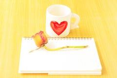 Taza de café, de rosas y de libro en la tabla de madera Foto de archivo
