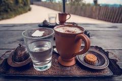 Taza de café, de un vidrio de agua y de galletas en la tabla de madera Fotos de archivo