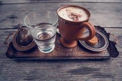 Taza de café, de un vidrio de agua y de galletas en la tabla de madera Foto de archivo libre de regalías