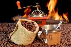 Taza de café del acero inoxidable y amoladora vieja con las habas Fotografía de archivo