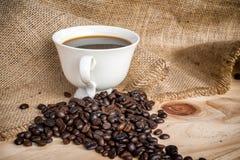 Taza de café del americano y de granos de café Foto de archivo