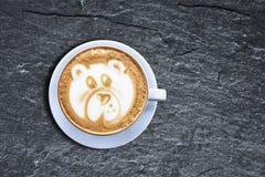 Taza de café del arte del latte del oso de peluche en el esquisto negro texturizado con el obl fotografía de archivo libre de regalías