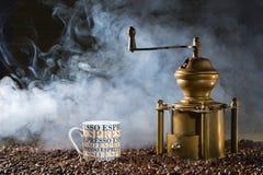 Taza de café del café express cerca de la amoladora de café vieja, contra la perspectiva del café de granos Fotos de archivo